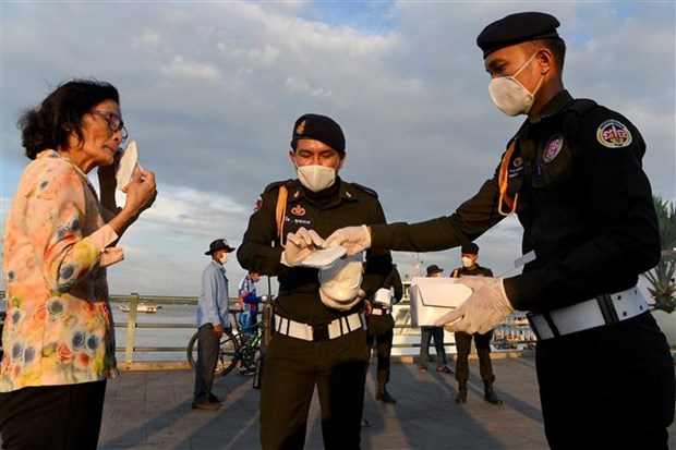 Cảnh sát phát khẩu trang miễn phí cho người dân tại Phnom Penh, Campuchia. (Ảnh: AFP/TTXVN)