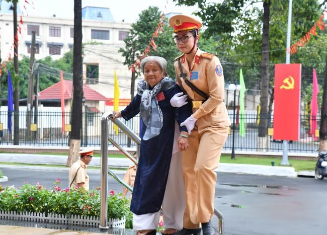 Nữ chiến sĩ CSGT dìu Mẹ Việt Nam anh hùng đến tham dự đại hội.