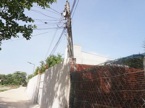 Trụ điện bên trong hàng rào nhà dân